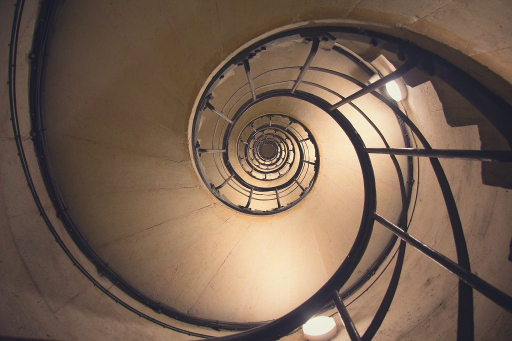 A shot looking up at a spiral staircase reminiscent of the golden ratio